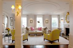 Picture frame moldings on the walls and curved molding on the ceiling add architectural interest. A custom curved couch takes center stage in the living room.