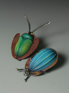 Coleoptera Pendant: The bodies are made from sycamore - turned and carved or pyrographed before being airbrushed with acrylic inks. The dotted ones are textured with acrylic resin. The copper is often textured with a subtle hammered pattern and heat treated to achieve the rich dappled colours. Some also have reclaimed 18ct gold eyes.