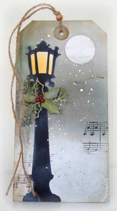 This is for Loll's second day of the 12 tags of Christmas. These are so much fun to do! The background was done with Infusions after masking the moon. I avoided using the powders on the lower half of the tag. I stamped music randomly over the backgrounds. I've had this Tim Holtz lamp post for years and never used it. After die cutting it I cut off the lights on the sides of it then sponged in white to give it a bit of a frosty look. I used a bit of watercolor to bring cloud...