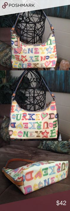 Dooney & Bourke Graffiti Logo Shoulder Bag Dooney & Bourke logo graffiti shoulder bag with zip closure and one interior zip pocket. Color Multi Color. Material Leather. Measurements 6 tall x 9 wide x 2 1/2 depth x 7 3/4 strap drop Dooney & Bourke Bags Shoulder Bags