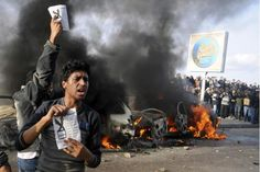"In this Friday, Dec. 14, 2012 file photo, opponents of Egyptian President Mohammed Morsi hold pamphlets urging a ""no vote"" on a constitutional referendum as cars burn during clashes between supporters and opponents of President Mohammed Morsi in Alexandria, Egypt. This Mediterranean city with a cosmopolitan heritage, now an Islamist stronghold, is often seen as a predictor of Egypt's trends. So a ferocious battle between sword-wielding Islamists and ro"