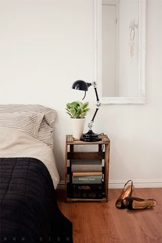 White bedroom. Old wooden box as bedside table. Nice bedside lamp.