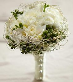 White roses, spray roses, freesia and hydrangea are accented with green hypericum berries and with an elegant gold wire bouquet collar and ivory pearls.