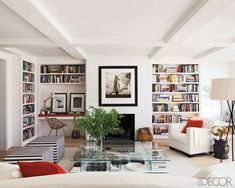 In the library of a Nantucket house ottomans by Antonio Citterio and a linen-upholstered armchair by Christian Liaigre surround a cocktail table by Piero Lissoni. The walls, brick fireplace, and custom-made bookshelves are coated in Country Stove White by Ralph Lauren Paint. Tour the entire home.