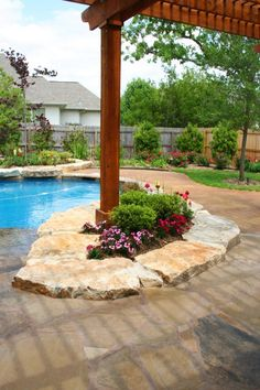 Slabs of stone around posts as flower beds. Neat idea for patio posts.