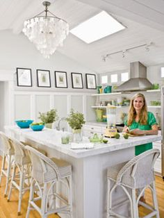 "This homeowner splurged on thick marble countertops. ""They get the most use, so they need to be -- and look -- substantial,"" says designer Jill Johnson. A capiz shell chandelier and wicker barstools are perfect shades of white in this crisp kitchen."