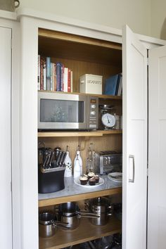 Tall bi-fold doors in a white kitchen reveal marble and wooden shelving in a larder for appliances, books, pots and pans storage. Kitchen designed by Giles Slater for Figura