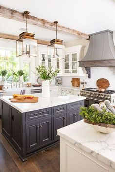 """Rustic Elegance in a California Farmhouse - Romantic Homes : the dark hood above the stove adds a stunning contrast to the rest of the kitchen with its white honed marble countertops. """"It's a custom designed zinc,"""" Karen says. """"The corbels are antique. Classic Kitchen, Farmhouse Style Kitchen, Modern Farmhouse Kitchens, Home Decor Kitchen, Home Kitchens, Small Kitchens, Kitchen Rustic, Rustic Farmhouse, Romantic Kitchen"""