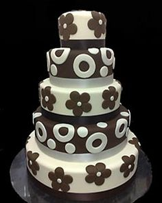 Five tier brown and white funky wedding cake decorated with white fondant circles and brown fondant flowers. From www.debbiebone.co.uk