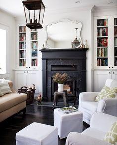 black fireplace, lantern, furniture arrangement, built-in bookshelves with glass doors, mirror above mantel