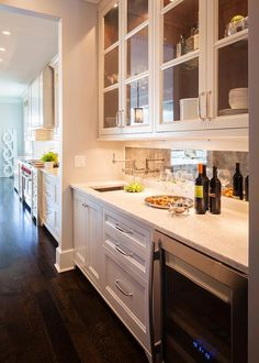 Chic butler's pantry features glass upper cabinets and white lower cabinets paired with white marble countertops and an antiqued mirrored backsplash.
