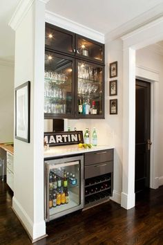 This small home bar was installed with a passthrough to an office area, and is fully stocked with a mini fridge, wine racks, and plenty of glassware storage.