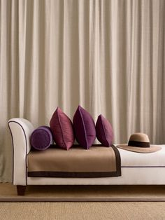 Colour scheme (backup) - cream / beige, burgundy, brown. (white couch in front of creme drapes with purple pillows and a hat on the couch)