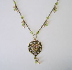 """February Challenge:  """"Heartsong"""" .... a classic necklace for casual or evening wear.  A beautiful brass heart base is embellished with a brass heart with roses charm, delicately tinted with green and pink, bringing Black Hills gold to mind.  A simple chain with glass bead dangles complete a classic and classy look.   www.facebook.com/NovegattiDesigns"""