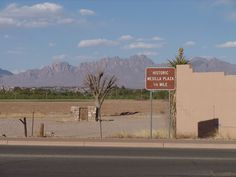 Sign for Historic Mesilla Plaza with views of the Organ Mountains.