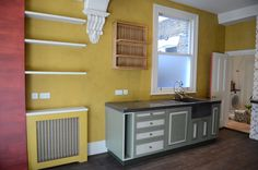 kitchen, base units with concrete worktop and sink. oak wall plate rack