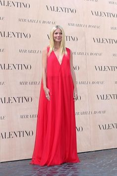"""Gwyneth Paltrow, a """"friend of the house,"""" as  Valentino tweeted, wore a red dress to take in the haute couture clothes come down the runway. Sitting with Maison Valentino himself and the designer's partner Giancarlo Giammetti, the Goop.com founder encapsulated summer simplicity in an elevated maxi dress, her hair styled stick straight, natural makeup, and no jewelry."""
