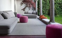 Gray outdoor sofa and purple handwoven stool on the terrace