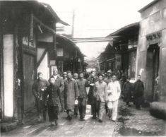 1942- Four Doolittle Raid crewmen, who bailed out over China from Aircraft #14, are escorted in a Chinese village before being reunited with other airmen. Center right, his arm held by a Chinese is Col. John Hilger, who was injured.