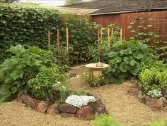 Want to increase the attractiveness of your veggie garden? Pitch out the concept of straight rows. Curved beds, stonework and a decorative piece turn the garden ornamental.