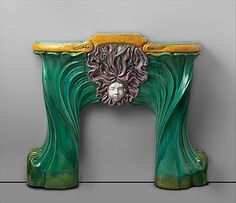 This fireplace is made of stoneware, a dense ceramic body that is highly durable. Its strong, sculptural design reflects the popularity of the Art Nouveau style. The twisting forms of the vertical sides and the complex, curving shapes of the hair above the mask are characteristic of Art Nouveau design, which emphasized stylized, sinuous lines and commonly employed motifs from the natural world. The fireplace is signed 'Muller/Luneville' | JV