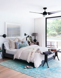 Bedroom with a blue rug and mismatched nighstands