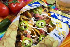 GOYA Nachos – Choice of Mojo chicken or pork, garlic yuca chips, jalapeno cheese sauce, black beans, jalapenos, salsa and sour cream. – GOYA Latin Grill, Section 105
