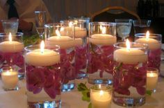floating candles and flowers in glass tumblers? Staggering heights and votives mixed in around glasses.