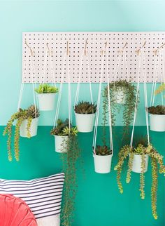 a peg board hanging planter DIY // how to display plants in a small space // love the teal wall!