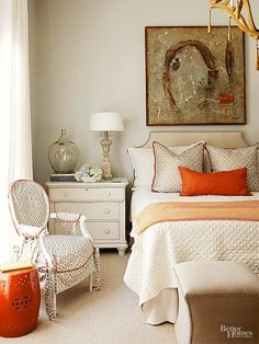 Blue is the longstanding cottage champ, but this master bedroom isn't afraid to deviate. The collected-over-time pieces get a wake-up call thanks to orange accents. Other common denominators weave throughout the room and repeat: The pillow and chair fabrics match, as do the nailhead trim on the headboard and ottomans. /
