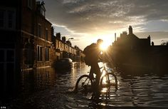 Travel disruption: As the sun set in Carlisle a man was pictured riding his bicycle throug...