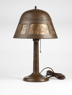 A rare Albert Berry hammered copper & mica lamp, Early 20th century, signed to base in script ''Albert Berry'' (1878 - 1967, Juneau, Alaska / Seattle, WA), the riveted bell-form shade with three wide rectangular cut-outs alternating with three pairs of narrow rectangular cut-outs, over a single socket on a riveted spreading cylindrical stem issuing from a riveted collar on a slightly domed circular base.