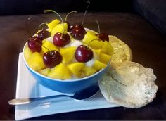 Homemade one ingredient banana ice cream, toped with mango, cherries and sided with a butter covered English muffin.