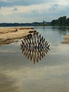 Ludoviv Fesson creates landart using water surface as a mirror.