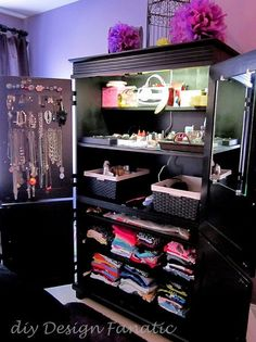 organized armoire, repurposing upcycling, The left top door of the armoire holds jewelry a mirror is mounted on the right top door The baskets hold hair products and tools and folded tshirts are on roll out shelves in the lower part of the armoire