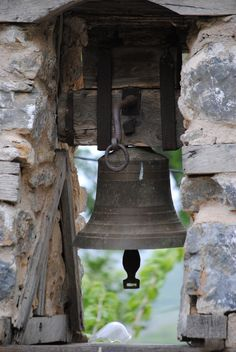 church bell mounted in wood and stone frame