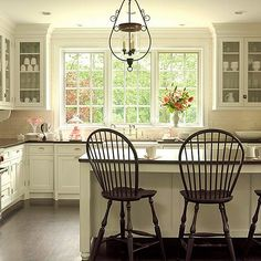 Love idea of white kitchen with windsor style chairs at bar/island  White Kitchen. Off White Kitchen Design. How soothing. I love the cream white cabinet paint color in this kitchen. #WhiteKitchen #Kitchen