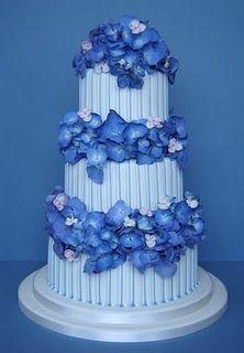 Stripy three tier white wedding cake with blue hydrangeas.