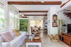 Integração de sala de estar, jantar e cozinha. Vigas de madeira aparentes e sofá branco.
