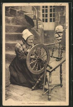 I know why this woman is gritting her teeth if she has any. If you look close you can see there is no flyer or bobbin. The wool is coming from the distaff over the wheel and back around to her hand. If she was an old spinner and it was me, I would be a bit ticked that someone thought this was real spinning and made me pose in such a way.