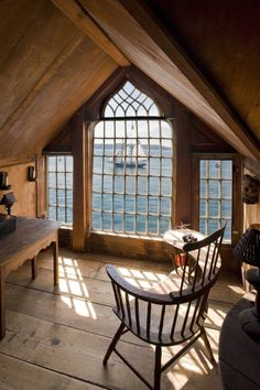 What a view! And the windows.... The plain wood bareness of the room is really interesting too