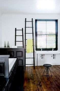 Chic bathroom décor with two ladders, black cabinets, and white sink and tub