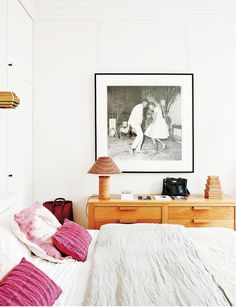 """A neutral hued bedroom gets a shot of color from rich dark pink throw pillows on the bed. See the rest of this gorgeous French apartment on """"Inside an Eclectic Parisian Pad"""" on MyDomaine -- Designer: Sandra Behaumou, Photographer: Montse Garriga Source: Elle Decor España"""