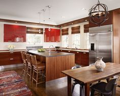 lacquered rouge upper cabinets + rich wood + stainless steel detail in kitchen by mark ashby design