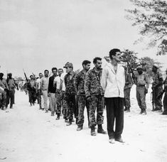 A group of captured U.S.-backed Cuban exiles, known as Brigade 2506, being lined up by Fidel Castro's soldiers at the Bahía de Cochinos (BAY OF PIGS), Cuba, following an unsuccessful invasion of the island.  -- April 1961.
