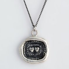 Long Distance Love Talisman Necklace / Pyrrha    This handcrafted talisman necklace reads Separated But Not Disunited. The two hearts side by side represent a love that is unaffected by distance or separation.