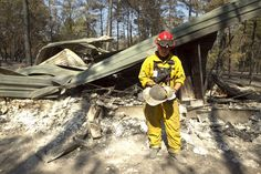 Capt. Alan Donaldson of the Bastrop Fire Department looks at a destroyed helmet where his home once stood in Bastrop's Circle D Estates