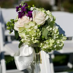The ceremony chairs were decorated with clusters of green hydrangeas, purple lisianthus and cream roses.