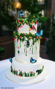 A beautiful wedding cake based on Costa Rican plants, leaves and vines with hand painted monkey and jaguar silhouettes hidden in the foliage. Hand painted wafer blue butterflies, bird of paradise, bromides and perching red macaws finish the design