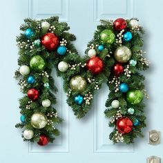 Monogram wreath decoration made with garland and Christmas ornaments.